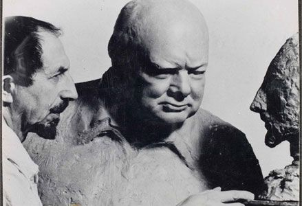 """About the photo: c1951, photograph of sculptor, Oscar Nemon, posing with Churchill's sculpted bust of Nemon, standing in front of Nemon' bust of Churchill. Although Nemon successfully fled Nazi persecution before the war, much of his family was not so fortunate. Nemon greatly admired Churchill, calling him """"one of the most remarkable personalities of all time."""" Churchill Archives Centre, The Nemon Papers, NEMO 4/3b"""