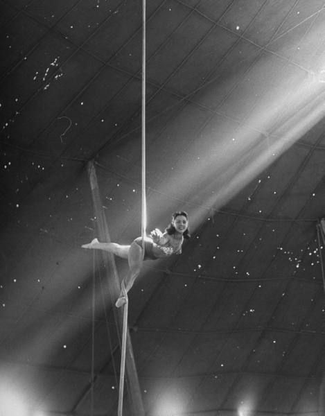 Circus Aerialist Bella Attardi, hanging on rope practicing aerial ballet (corde lisse) for Ringling Bros. Circus,1949 by Nina Leen