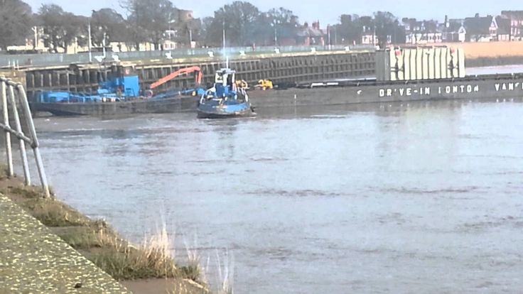 Tugs push a pontoon out of Goole docks in to river