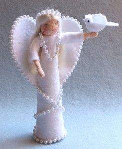 De vredesengel is 15 cm hoog en houdt een vredesduifje in haar hand. Ze is versierd met een kralenketting en haar haren zijn van zijdelont.