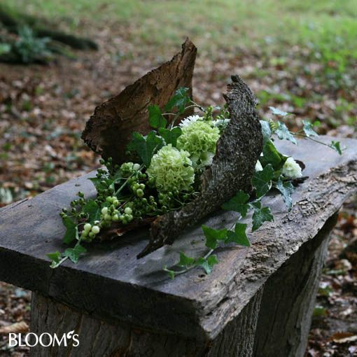 Inspiration [Only Image] & this description: The bark forms a bowl-shaped shell. Herein a watered fresh floral foam pad is attached, which is covered with moss and sullied with flowers and green vines. ~-> I think would be great with artificial arrangement too...