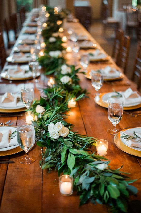 Rustic garland and candle covered wedding tables: http://www.stylemepretty.com/virginia-weddings/madison-virginia/2016/09/09/indoor-charlottesville-farm-style-wedding/ Photography: Ashley Cox - http://ashleypcox.com/