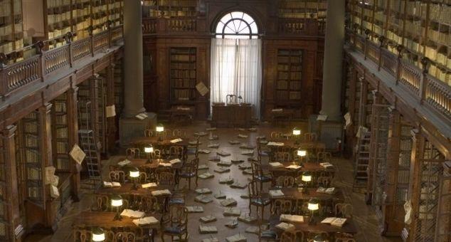 """""""CENTOCHIODI"""" di Ermanno Olmi. Scena iniziale: il custode di una biblioteca storica (ovvero la Biblioteca Universitaria di Bologna) trova la sala di lettura disseminata, per terra e sui tavoli, di libri aperti, ciascuno trafitto da un grosso chiodo."""