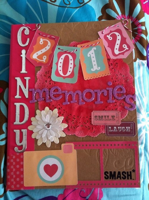 Cover of my Pink Smash Book <3      I huey misted a white doily and the 2012 banner, camera, and film strip are cuts from my Silhouette Cameo (:
