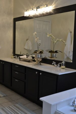 I love this idea with the black frame black cabinets, I would do grey walls but clever makeover for those huge mirrored bathrooms with no frame