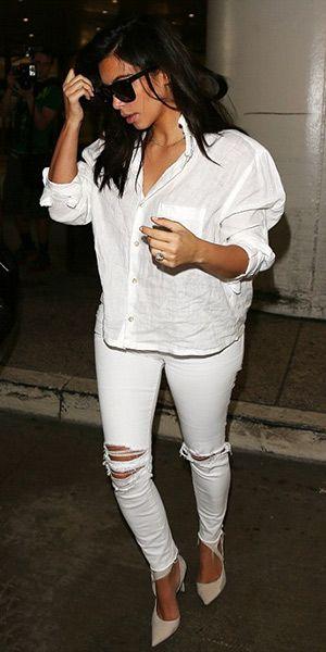 Kim Kardashian usando calça  jeans branca rasgada, scarpin de bico fino e camisa oversized branca.