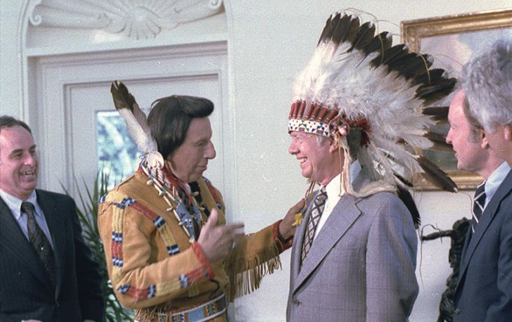 A photograph of Iron Eyes ody, a non-Indian, presenting then President Jimmy Carter with an eagle feather headdress.