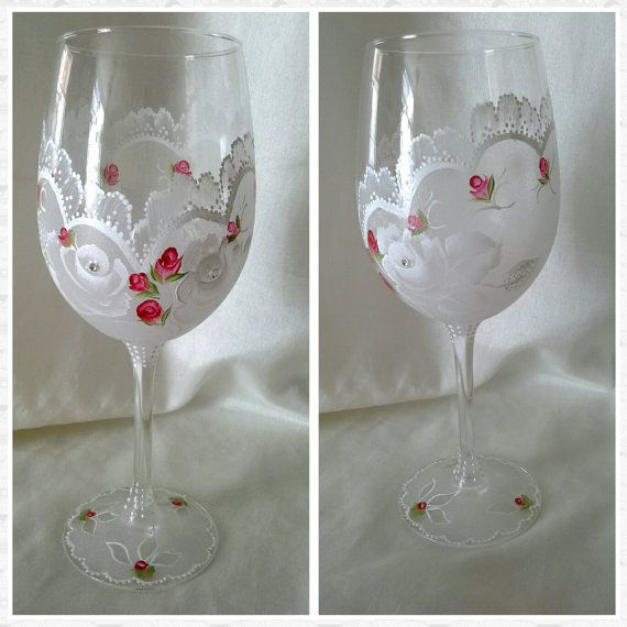 This large wine glass has been painted with pretty lace effect with white roses and small red rose buds.  Austrian crystals adorn the centre of the two white roses and add a beautiful shimmer to the glasses.   The glass was painted with enamel and then sealed and heat set for extra durability.   The price is for one glass but a matching pair can be made, please message me if you would like this .   There is lots of detail to this glass and it is a one of a kind original design.  It is hand…