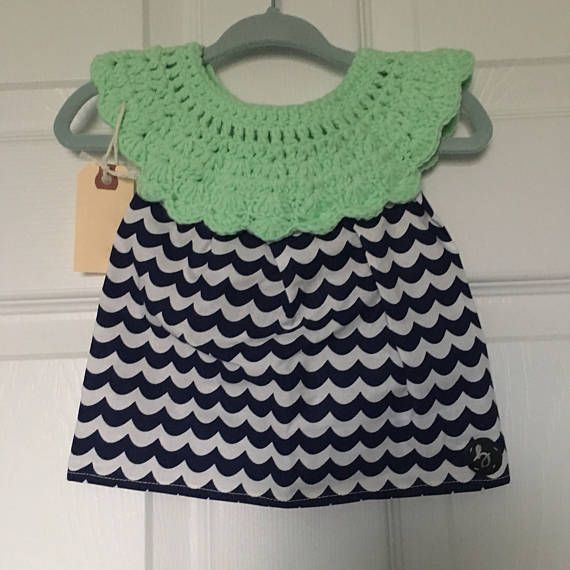 0-3 month size handmade baby girl dress with crochet top in mint cotton/nylon/polyester blend yarn with white & navy wave pattern cotton fabric skirt, fastened at the back with a button. Lightweight and pulls over the head.
