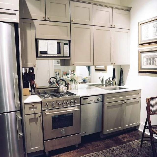 Gray cabinets with antique brass handles mirror instead of backsplash