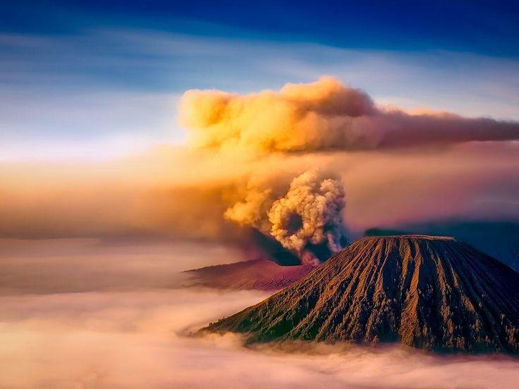 Der Bromo bricht bei Sonnenaufgang aus. Trotzdem wirkt die Atmosphäre friedlich und die goldenen Sonnenstrahlen erhellen den Vulkan und die ausgestoßene Asche. Foto: Kok Tien Sang  #Vulkan #Indonesien #Bromo