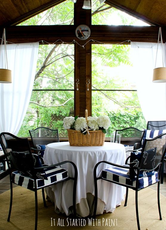 Screen Porch decorating ideas in navy and white; cedar screen porch with vaulted ceiling and privacy curtains decorated with navy and white pillows.