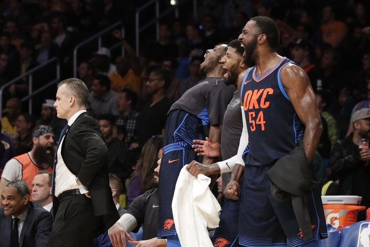 Standing behind Oklahoma City Thunder coach Billy Donovan, left, Patrick Patterson, from right, Paul George and Jerami Grant react to a dunk by Terrance Ferguson during the second half of the team's NBA basketball game against the Los Angeles Lakers, Wednesday, Jan. 3, 2018, in Los Angeles. The Thunder won 133-96. (AP Photo/Jae C. Hong)
