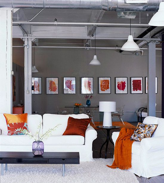 Add Color with Art  Colorful framed wall art pops. The dark gray of this loft's walls emphasizes the warm colors in the framed pieces. Pillows and throws bring the colors further into the room.    For a contemporary, graphic effect, frame pieces in identical white mats and black frames and hang them in a line across the wall. The line should be at eye level.