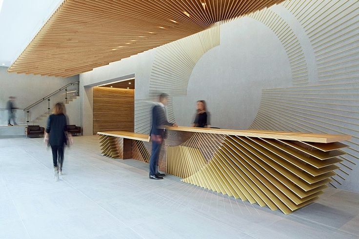 ampersand,soho london by hingston studio - the reception desk is made from one tonne of solid american oak, it's complimented with bespoke and polished brass slats.