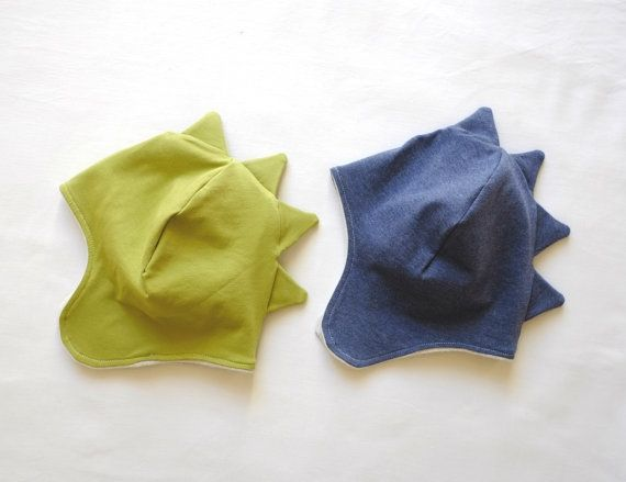Introducing our adorable, soft and cosy Dino Hat made from all organic cotton. Hat outer is made from organic blue jersey, and then is lined with a warm organic sweater fleece in off-white colour. This fabric is the highest quality and kind to your childs skin. This hat is the perfect addition to any fall and winter wardrobe for both boys and girls. The hat is made snug but there is stretch in the material for a close fit. Also features ear flaps which help keep babies ears and cheeks warm…
