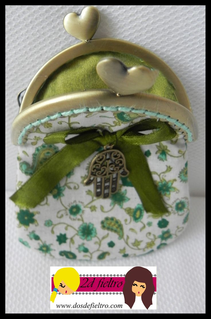 monedero boquilla metalica redonda con cierre de corazon, tela exterior blanca con dibujos de flores en tonos verdes, tela interior verde. Lazo verde con colgante mano fatima