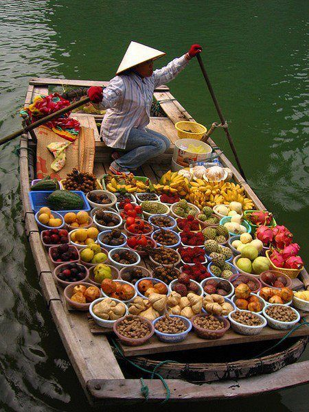 Somewhere in the East, beautiful palettes of food are transported in small boats to markets.
