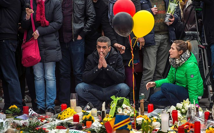 A man sits in front of a makeshift memorial to pay tribute to the victims of the Brussels attacks on the Place de la Bourse (Beursplein) in central Brussels