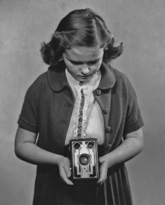 Brownie Camera: A girl taking a photograph with a Kodak box Brownie camera (circa 1935)