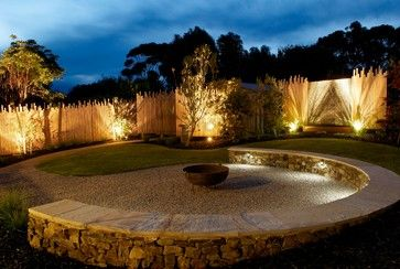 This curved half wall is lined with path lighting while the walls around the yard have accent lighting to shine light upward on the walls. The combination of these lighting elements build a warm and soft ambient light profile.