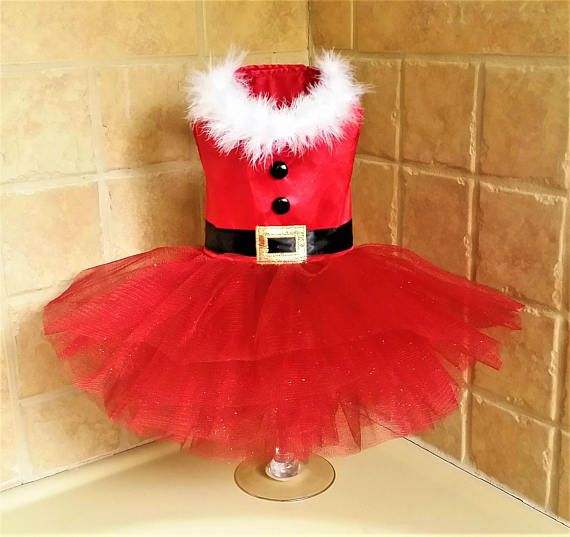 Dress A -Its almost Christmas! This Sassy Santa Tutu dress features a bright red bodice complete lined and adorned with white feather boa trim, black buttons, a classic black belt and gold buckle applique. The skirt has layers of puff tulle. Dress B -Santas cutest little helper!