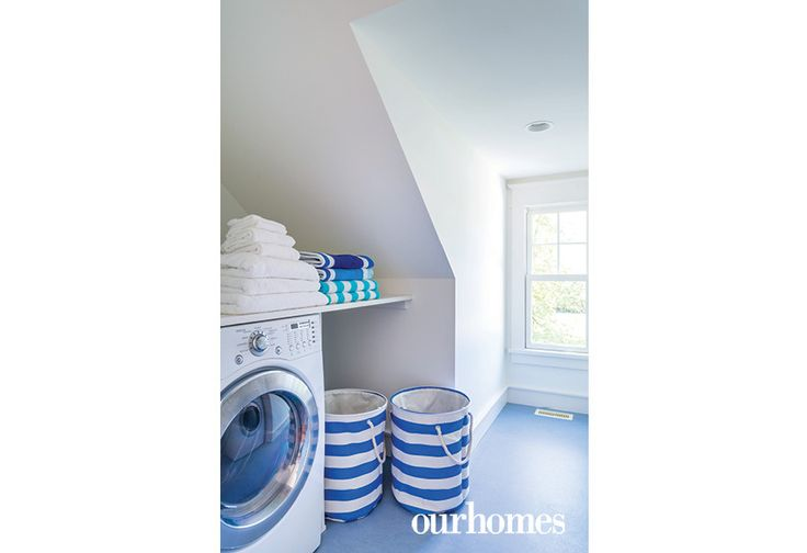 "A gabled window shines light into the second floor laundry room. The nautical theme is represented here as well, with blue-striped laundry hampers and blue beach towels.     See more of this home in ""Cape Cod Style Home on the Shores of Georgian Bay"" from OUR HOMES Southern Georgian Bay, Summer 2017 http://www.ourhomes.ca/articles/build/article/cape-cod-style-home-on-the-shores-of-georgian-bay"