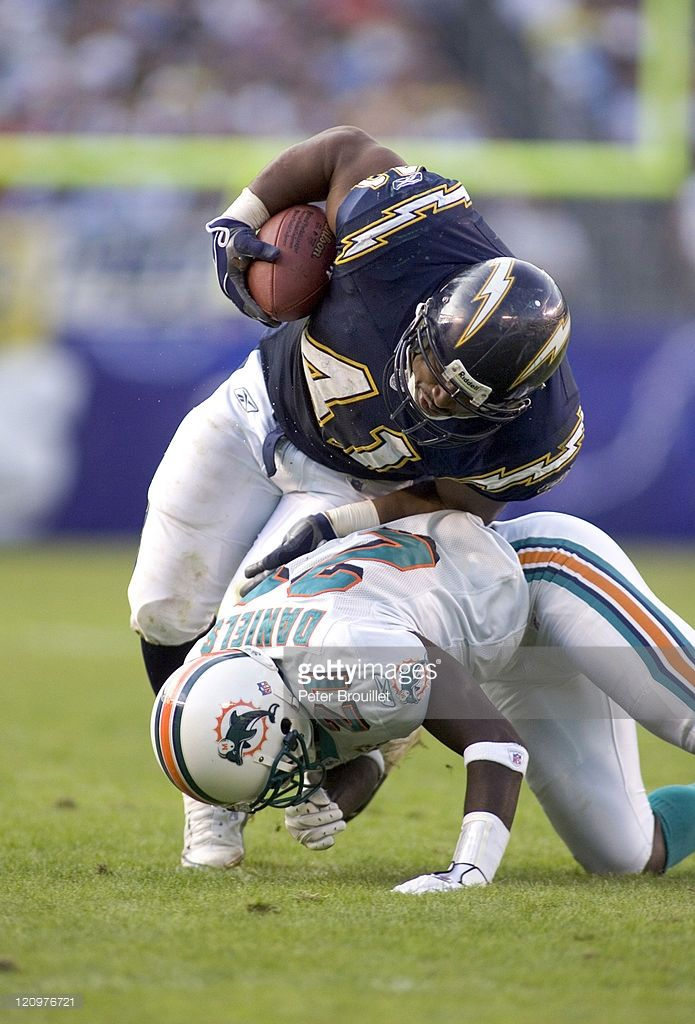 Lorenzo Neal fullback for the San Diego Chargers is tackled by #21 Travis Daniels in a game against the Miami Dolphins at Qualcomm Stadium in San Diego, California on December 11, 2005.