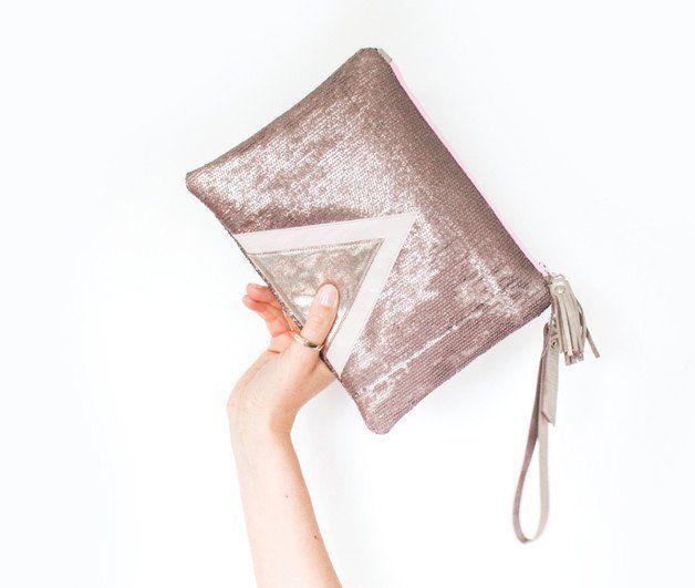 Diese kleine Clutch ist aus metallisch Rosa Pailletten Material mit geometrischer Lederapplikation. Die Tasche hat einen Kontrast Reissverschluss in rosa.  Leder Quaste und Tragriemen am...