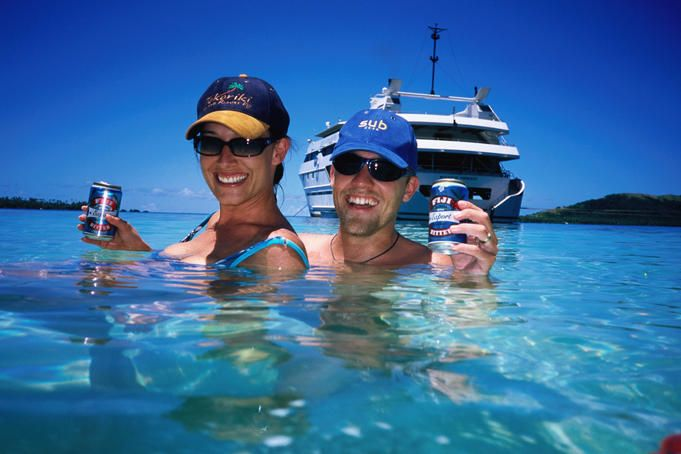 Couple enjoying beer in lagoon, Blue Lagoon cruise, Nanuya Lailai Island.