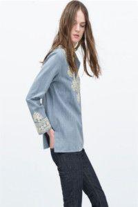 La blusa in denim firmata Zara. Ricami bianco avorio, tagli laterali e vestibilità morbida per questa proposta.
