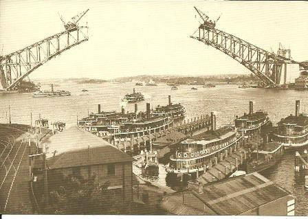 Sydney Harbour Bridge not yet complete when this photo of Sydney Harbour ferries was taken.