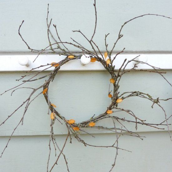 Make a simple autumn wreath out of twigs, leaves and a wire hanger.