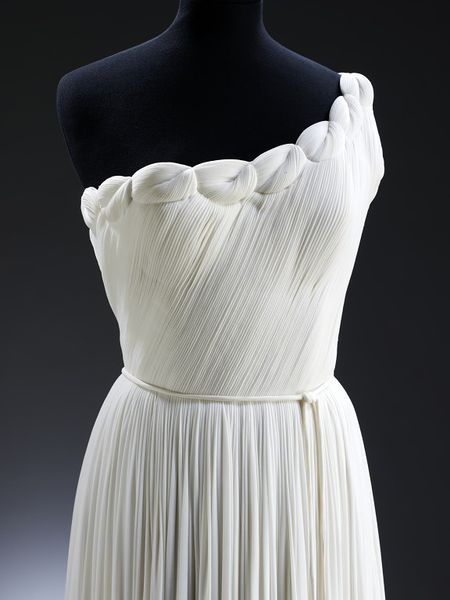 This evening dress is a replica of a 1955 design and was made especially for the Museum in 1971. Madame Grès trained as a sculptor and then turned to haute couture, becoming 'Alix', with premises in the Faubourg St Honoré in Paris. She re-opened at 1 rue de La Paix in 1941 as 'Grès'.