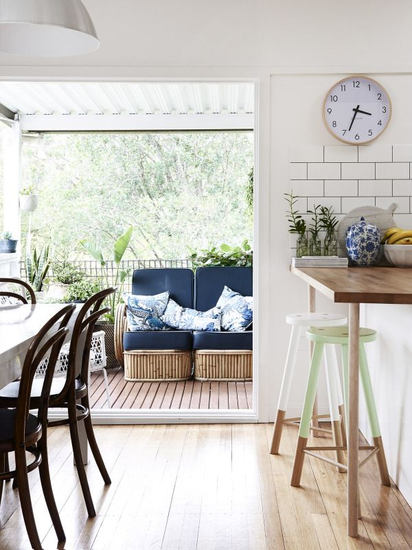Looking from dining area to back porch.  Green and white stools are from Green Cathedral. Clock from Yellow Bungalow in Bondi. Dining chairs are vintage Thonet Bentwoods. Sofa on deck is 2-piece Art Deco pretzel cane lounger. Photo – Eve Wilson, Production – Lucy Feagins / The Design Files