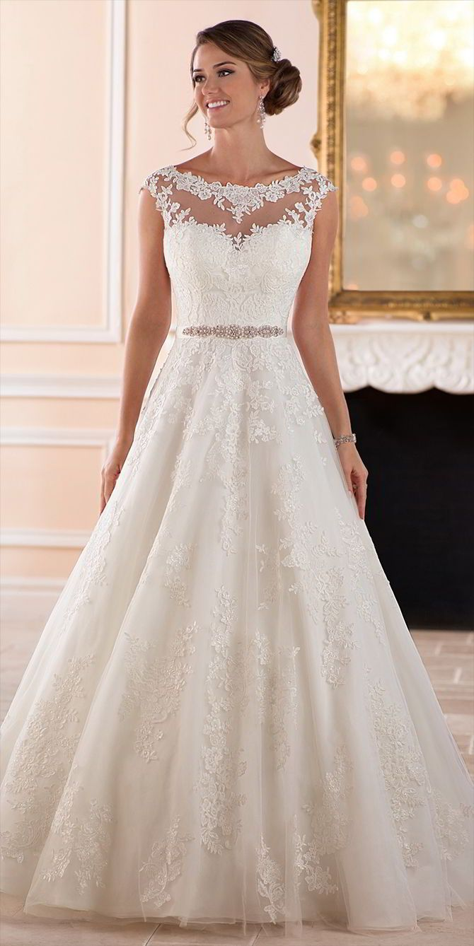 This traditional ball gown wedding dress from Stella York features lace over tulle in a soft A-line silhouette, perfect for the classic bride! The voluminous skirt feels full and flowy while remaining light-as-air as layers of tulle are adorned with delicate lace details that give off a unique effect. The illusion lace neckline, that highlights the blushing bride's face, continues to the back of the ball gown where floral patterned lace creates a stunning back. Fabric covered buttons finish