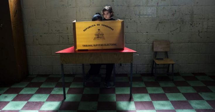 Lina Michel Colindres, 17 months, with her mother, Nely, at a voting booth in Tegucigalpa, Honduras, on Sunday. (Rodrigo Abd / AP)