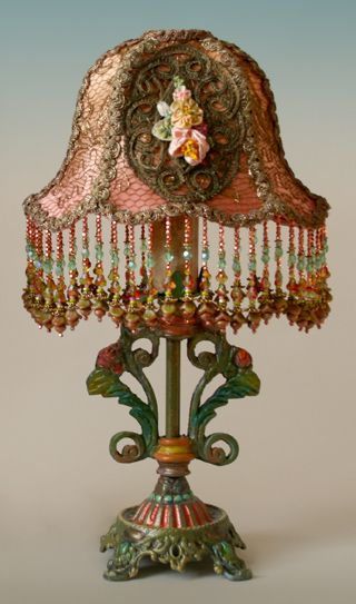 Pair of antique ornate table lamps with scrolls and roses hold a pair of small Gish shades dyed in shades of copper and apricot and covered in metallic gold lace and heavy metallic appliqués. circa 1920. Vintage silk ribbon rosettes adorn the center of the appliqués. Hand beaded fringe in copper, green and apricot tones finish the bottom.