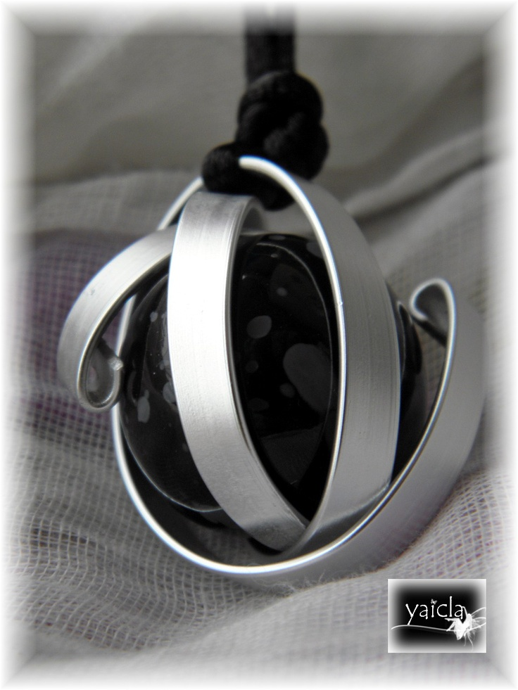 bola de madera tintada en negro y alrededor lleva unas laminas de hilo de aluminio plano en color plata.