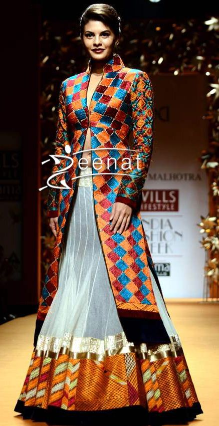 Jacqueline Fernandes in a marvellous Long Jacket Lehenga by designer Manish Malhotra. Jacqueline walks the ramp for WIFW Fall-Winter 2013. Ravishing colors orange, maroon, beige, golden, black and a hint of blue makes it all eminent with golden lace and gota patti around the lehenga.