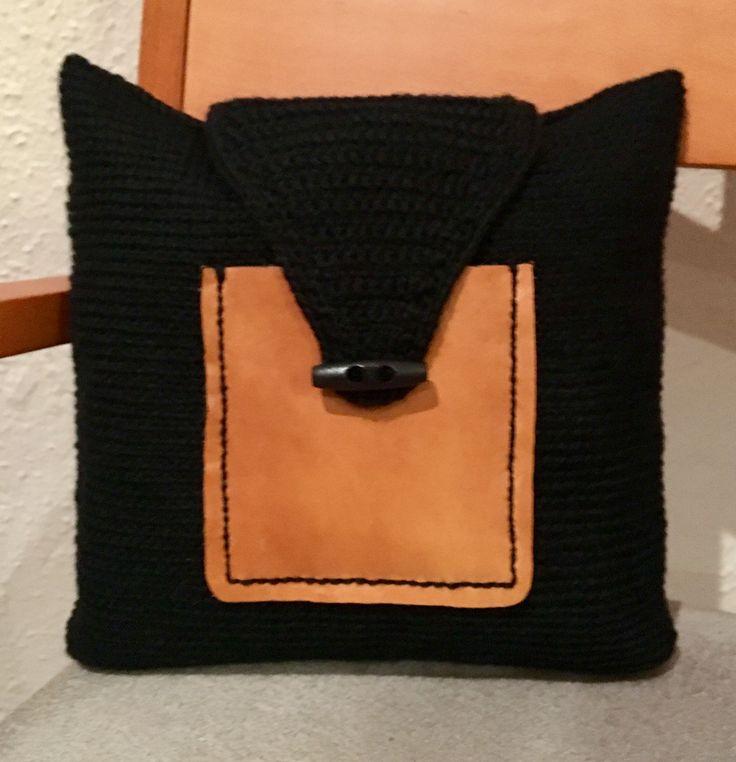 Clucht en crochet negro con bolsillo en piel marrón.