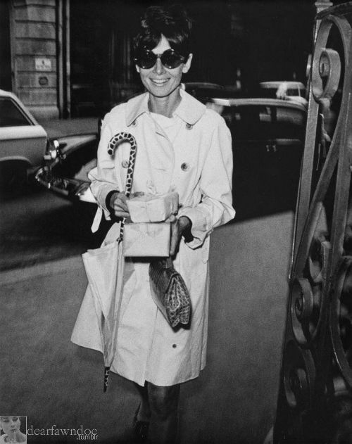 Audrey Hepburn photographed during her shopping in Paris (France), in March 1968. -Audrey was wearing Burberry trench coat, sunglasses of Oliver Goldsmith, Gucci handbag and holding her umbrella of Givenchy Nouvelle Boutique.