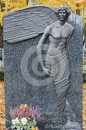 Angel and flowers  on the Tomb in Rakowicki cemetary in Krakow. Autumn time.