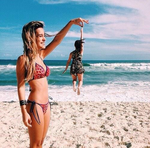 one girl holding a another one up at the beach