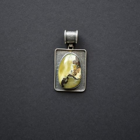 Silver pendant with amber of green pattern and an ornament