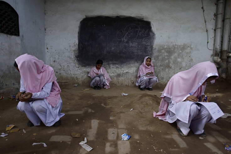 Pakistani girls sit amid graves whilst attending a test during their daily classes at a makeshift school managed in the boundary of a small graveyard in Gujranwala near Lahore, Pakistan, Thursday, April 19, 2012. Pakistani government allocate less then four per cent for education in the country of more the 180 million. (AP Photo/Muhammed Muheisen)