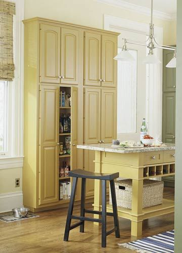 Custom Pantry Storage  Tall, shallow cabinets installed as part of a kitchen remodel efficiently utilize wall space between windows and the dining room pocket door.