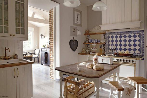 Zdjęcie: rustykalna kuchnia z białymi meblami i szafirowo-białą glazurą pod drewnianym okapem