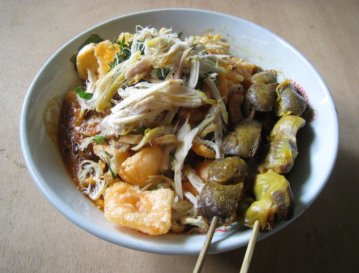 A Bubur Ayam (chicken rice congee) with chicken liver and gizzard satay, sold by travelling vendor cart that frequenting kampung or residential area every morning in Jakarta, Indonesia.