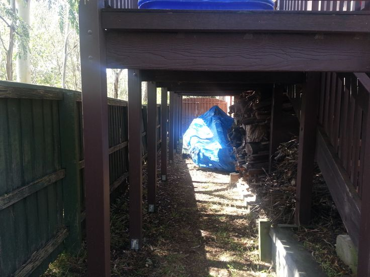 Looking under the verandah.  Under the blue tarp is a boat